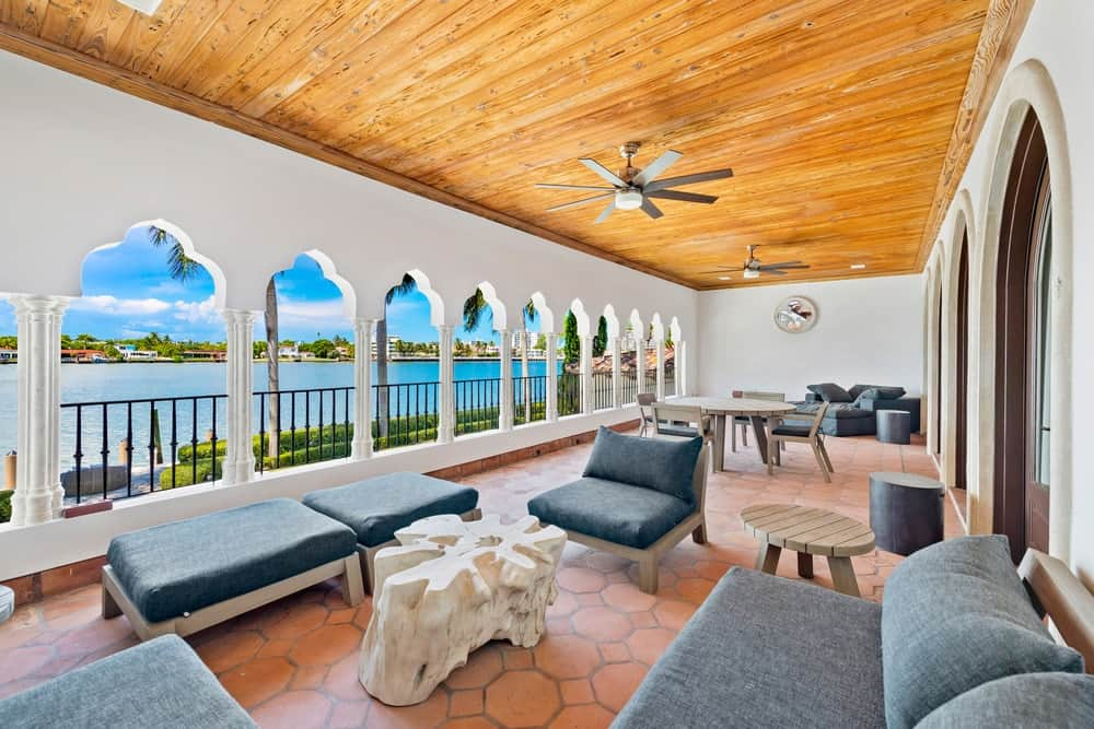 This is the covered patio lined with arches on one side, has a wooden ceiling, a sitting area and an outdoor dining area at the far end. Image courtesy of Toptenrealestatedeals.com.