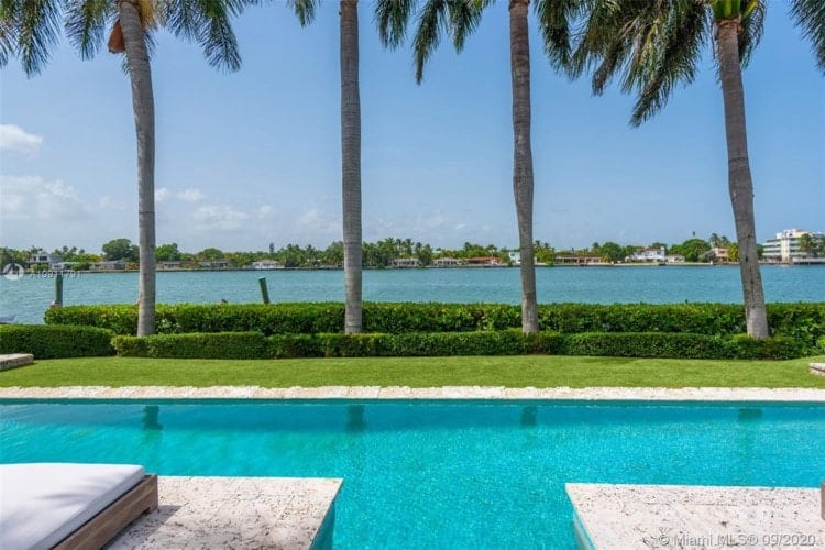 This is a look at the side of the pool that is adorned with lush landscaping of grass lawn, shrubs and tall coconut trees. Image courtesy of Toptenrealestatedeals.com.
