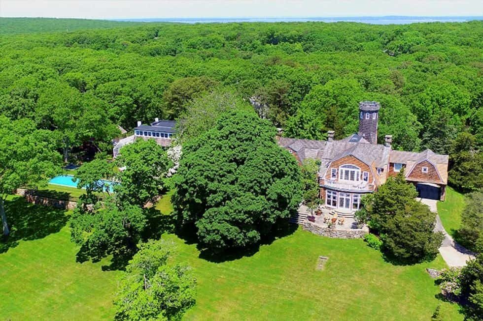 This is an aerial view of the house showcasing the earthy tones of the house exteriors complemented by the lush green landscape of tall trees, grass lawns and shrubs. Image courtesy of Toptenrealestatedeals.com.