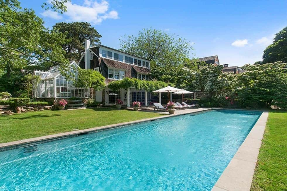 This is a look at the back of the house with a large swimming pool and lush landscaping of grass lawns, shrubs and tall trees to complement the glass walls and windows of the house. Image courtesy of Toptenrealestatedeals.com.