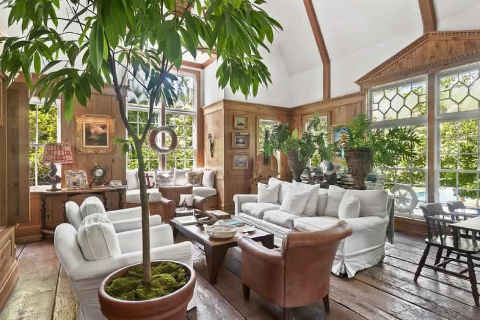 The cozy family room has simple wooden tones on its floor, walls and tall ceiling that are complemented by the green leaves of the various potted plants contrasted by the light beige sofas. Image courtesy of Toptenrealestatedeals.com.