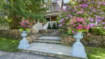 This is a look at the front of the house featuring a set of concrete steps leading to the main entrance adorned with flowers on planters, tall trees and thick shrubs. Image courtesy of Toptenrealestatedeals.com.