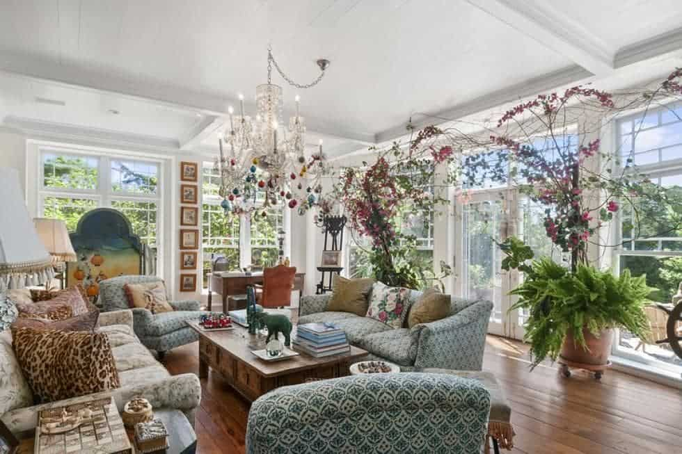 This is the formal living room with a gray patterned sofa set paired iwth a wooden coffee table that blends with the hardwood flooring. These are then complemented by the chandelier and potted plants. Image courtesy of Toptenrealestatedeals.com.