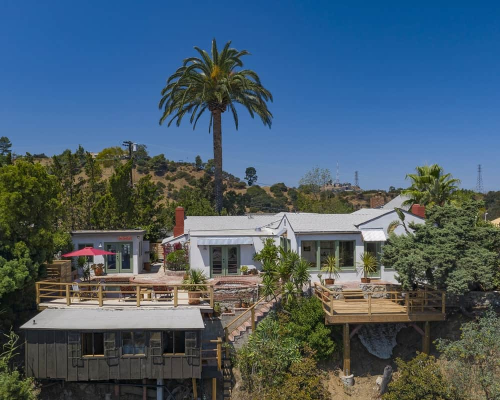 This is an aerial view of the side of the house that faces the sweeping view of the city below. Here you can see various outdoor areas to maximize the view built on wooden deck platforms and complemented by the surrounding tropical landscaping. Image courtesy of Toptenrealestatedeals.com.