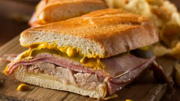 Slice of traditional Cuban sandwich with pork and mustard.