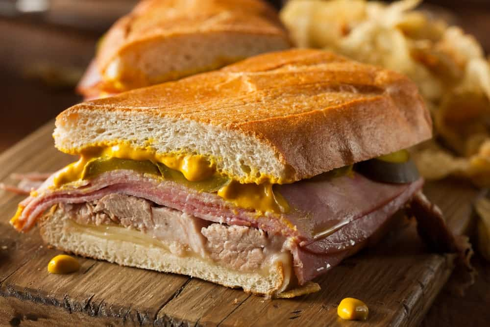 A slice of traditional Cuban sandwich with pork and mustard.