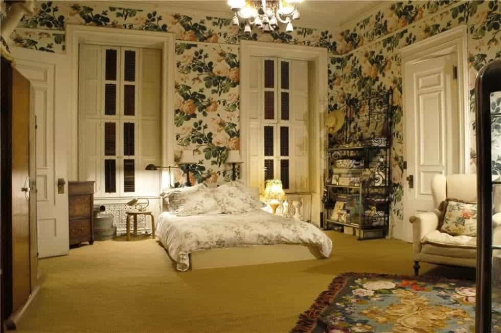 The bedroom has floral wallpaper that complements the white frames of the tall windws and the floral sheets of the bed on a beige carpeted flooring. Image courtesy of Toptenrealestatedeals.com.