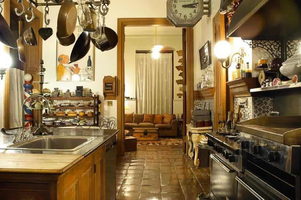 This is a close look at the kitchen that has hanging pots and pans over the kitchen island across from the stainless steel oven. These are all complemented by the warm lights and the terracotta flooring. Image courtesy of Toptenrealestatedeals.com.