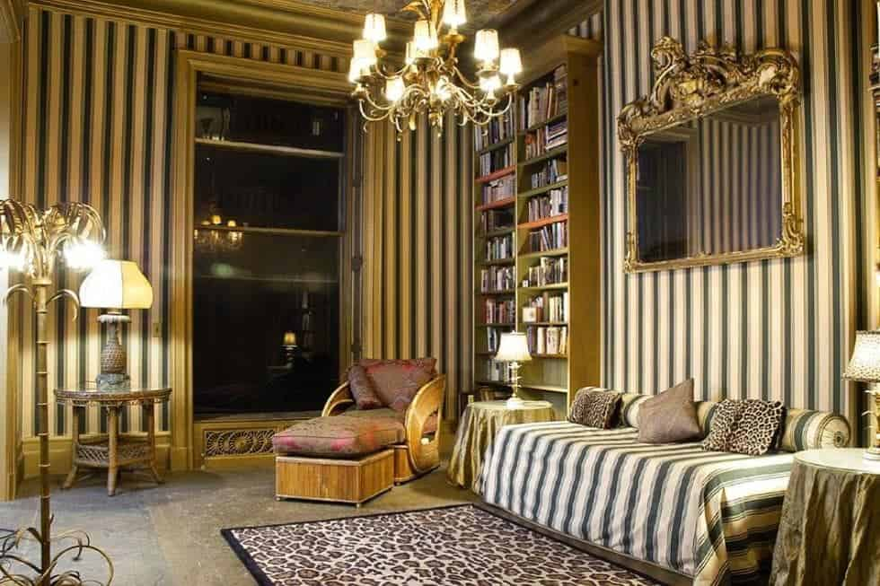 This is the spacious library with a tall ceiling that hangs a large chandelier, striped wallpaper on the walls that pair with the striped sofa beside the built-in bookshelves and below the mirror. Image courtesy of Toptenrealestatedeals.com.