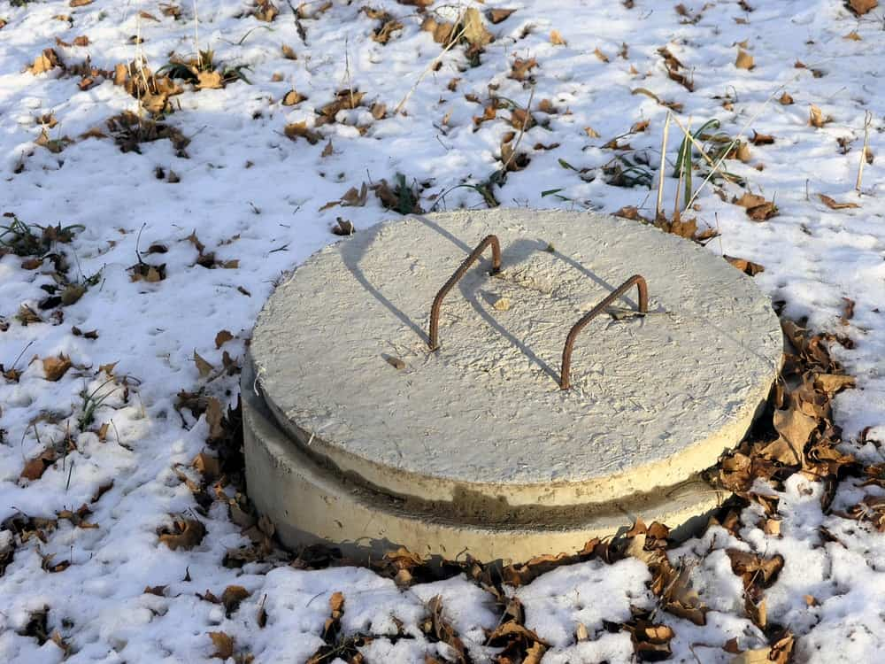 A layer of snow surrounding the concrete cover of the septic system.