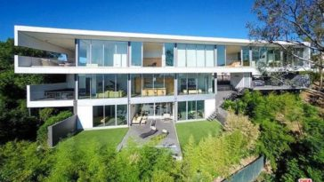 This is an aerial view of the house showcasing the three levels of the house made of bright white materials and glass walls. You can also see here the various balconies and interior. Image courtesy of Toptenrealestatedeals.com.