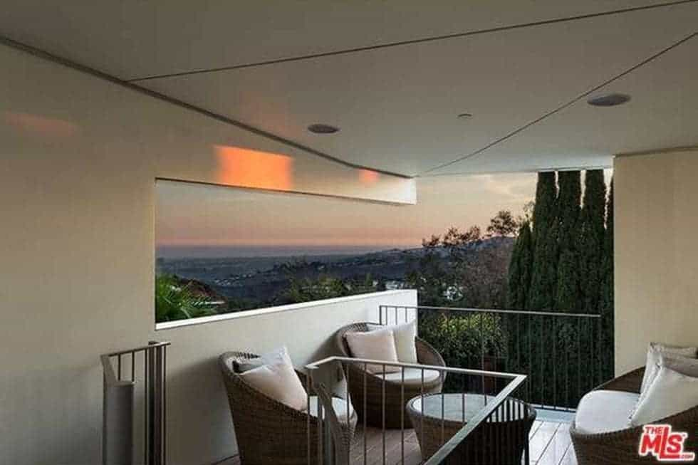 This is the balcony fitted with comfortable cushioned chairs surrounding a small round coffee table and has a background of the city below. Image courtesy of Toptenrealestatedeals.com.
