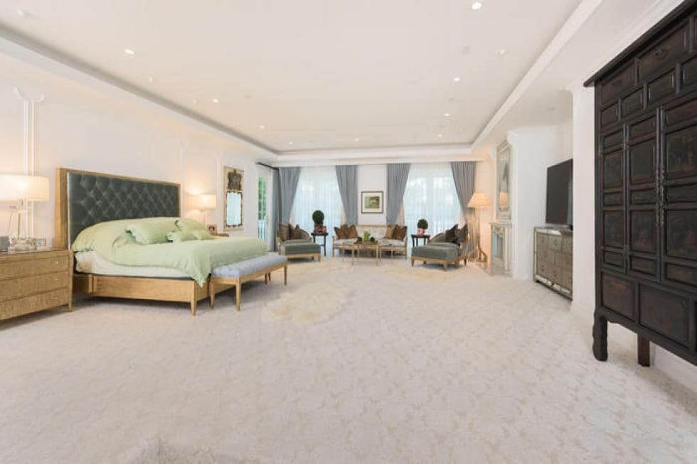 The spacious primary bedroom has wooden elements like the bed and its bedside drawers that stand out against the beige walls and beige flooring. Image courtesy of Toptenrealestatedeals.com.