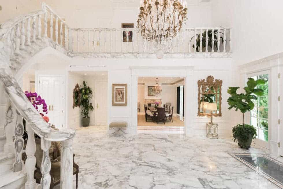 Upon entry of the mansion, you are welcomed by this white marble foyer with a grand chandelier hanging in the middle of the tall ceiling. Image courtesy of Toptenrealestatedeals.com.