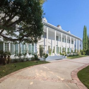 This is the front view of the white greek-revival style mansion with a wide walkway, wide balconies and multiple dormer windows. Image courtesy of Toptenrealestatedeals.com.