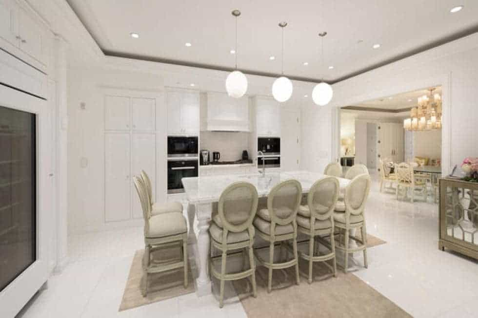 The kitchen has three spherical pendant lights hanging over the white marble kitchen island that is paired with beige stools for the breakfast bar. Image courtesy of Toptenrealestatedeals.com.