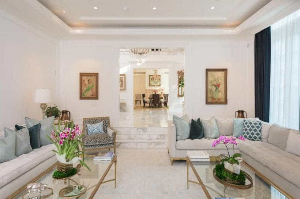 This is the light beige living room with a tray ceiling, beige walls that match the beige sofa sets and glass-top coffee tables. Image courtesy of Toptenrealestatedeals.com.
