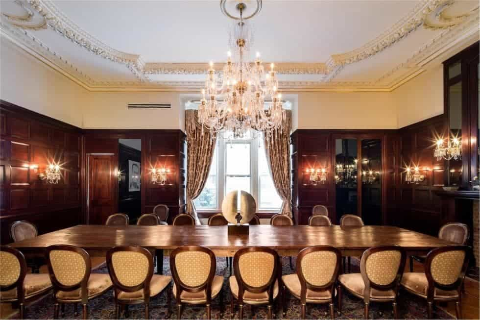 This is the formal dining room with a long wooden dining table surrounded by oval-backed cushioned chairs and topped with a large crystal chandelier. These are then complemented by the wood-paneled walls. Image courtesy of Toptenrealestatedeals.com.