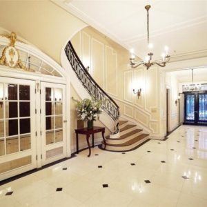 Upon entry of the mansion, you are welcomed by this grand marble foyer with bright beige walls, floor and ceiling. These are then complemented by the console table, chandelier and French doors. Image courtesy of Toptenrealestatedeals.com.