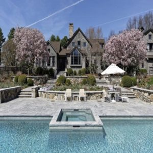 This is an aerial view of the house with stone walls and grayish tone to its exteriors that are complemented by the colorful trees of the landscape along with the large pool with spa. Image courtesy of Toptenrealestatedeals.com.