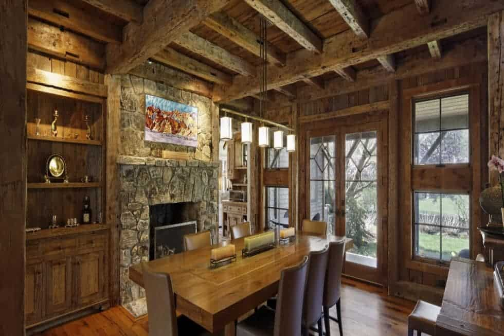 This is the dining room with a rustic feel to its mosaic stone fireplace, wooden beamed ceiling and the row of lights over the wooden dining table. Image courtesy of Toptenrealestatedeals.com.