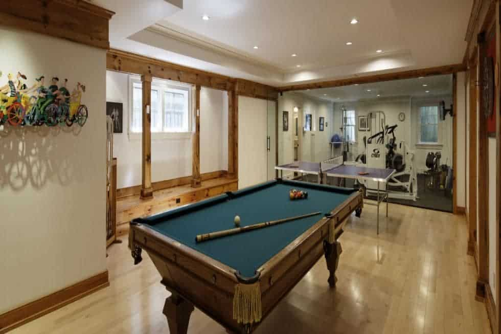 The large game room has a pool table, a ping pong table and a gym at the far end of the room with various equipment. Image courtesy of Toptenrealestatedeals.com.