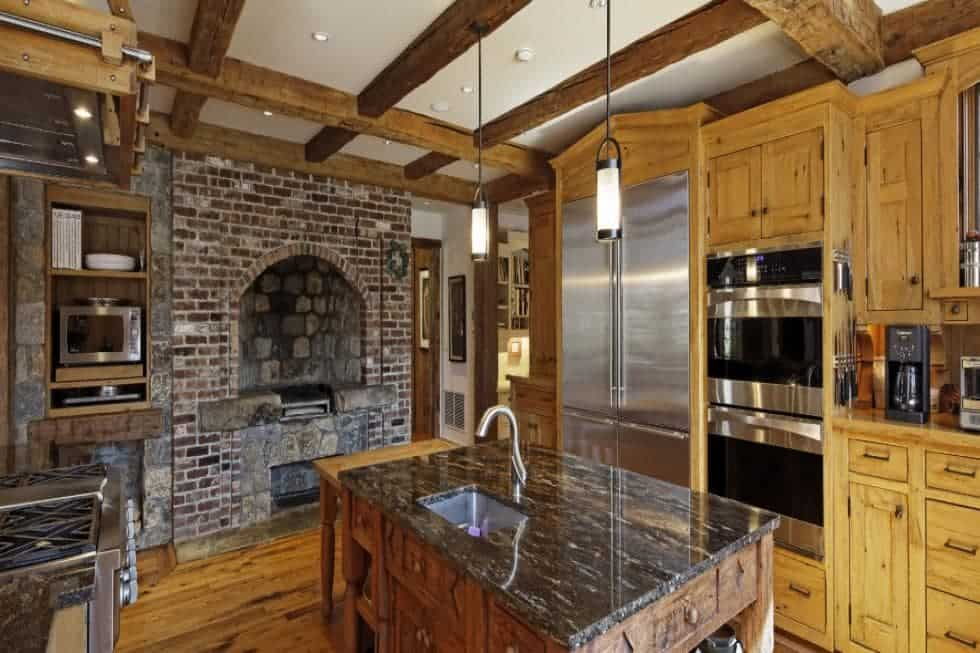 This is the rustic kitchen with a red brick wood-burning oven at the fire wall. The kitchen also has wooden cabinetry that matches the beams of the ceiling and the hardwood flooring. Image courtesy of Toptenrealestatedeals.com.