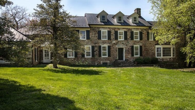 This is a view of the back of the house with stone walls, multiple windows, dormer windows and chimneys complemented by the landscape. Image courtesy of Toptenrealestatedeals.com.