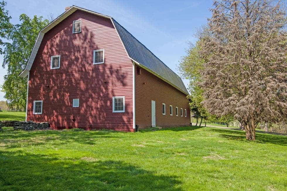 This is the large wooden barn inside the farm with red exterior walls and a gambrel roof. Image courtesy of Toptenrealestatedeals.com.