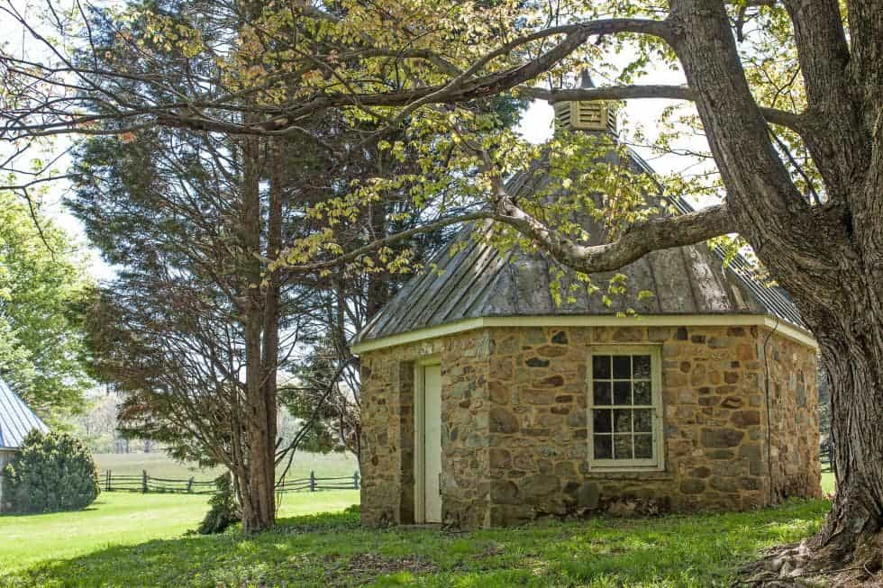 This is a look at the guest house with a small stone structure topped with a tall tin roof adorned by the tall trees. Image courtesy of Toptenrealestatedeals.com.