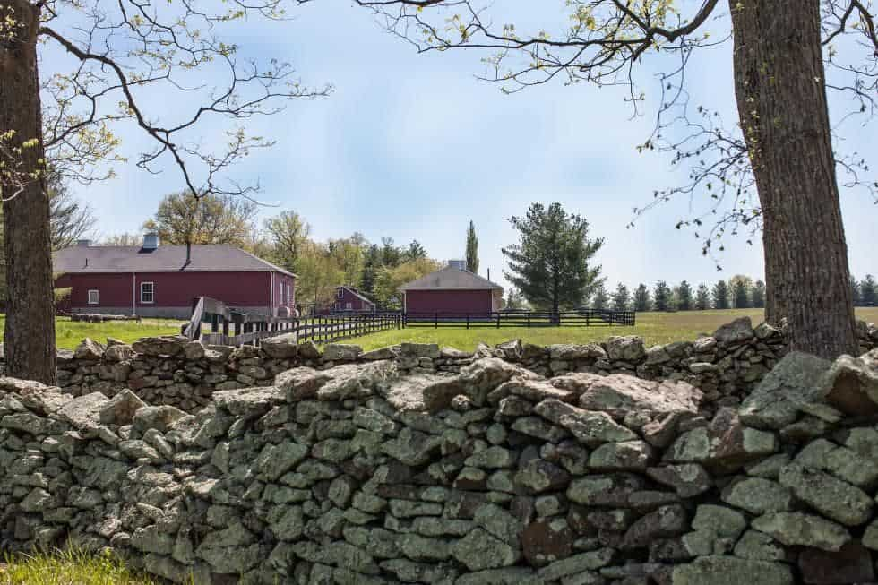 This is a look at the landscape of the farm featuring stacked stone walls lining the sides of the walkways and driveways. Image courtesy of Toptenrealestatedeals.com.