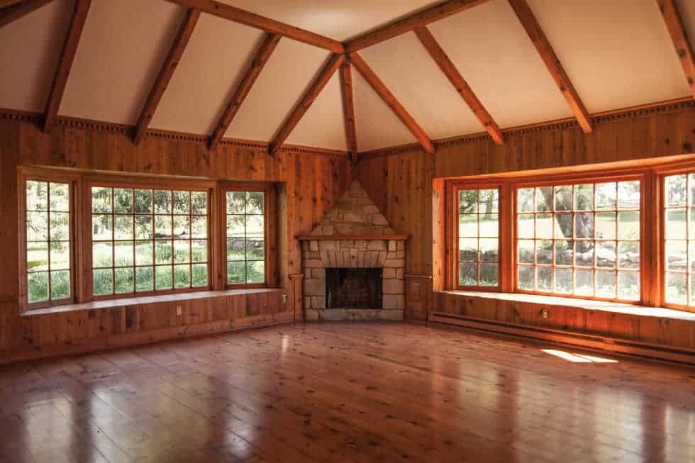 This look at the interior of the main house showcases the large living room with a corner fireplace on the far side in between two large windows that bring in natural lighting for the wooden tones of the floor, walls and ceiling beams. Image courtesy of Toptenrealestatedeals.com.