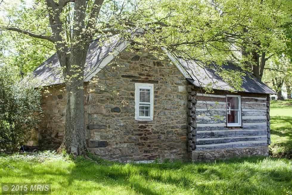 This is the historic log cabin inside the property with mosaic stone walls, tin roof and complemented by the surrounding landscape of trees and grass. Image courtesy of Toptenrealestatedeals.com.