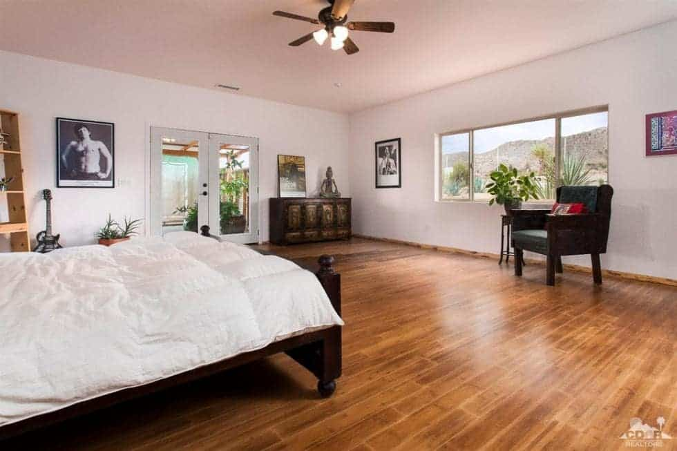 This is the bedroom with a dark wooden sleigh bed that matches the hardwood flooring. Across from the bed is a reading nook by the window. Image courtesy of Toptenrealestatedeals.com.
