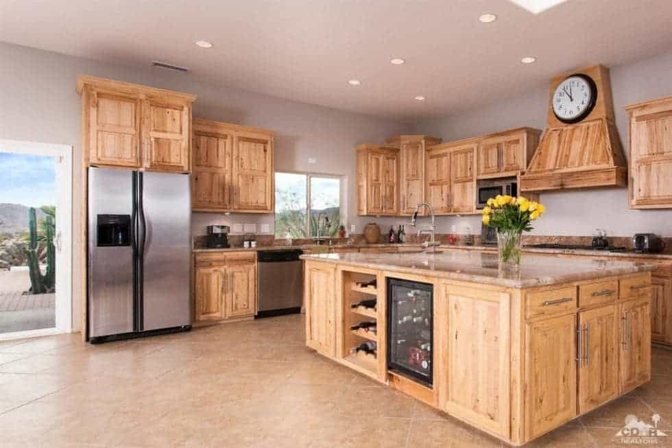 This is the large kitchen with wooden cabinetry on the walls to match the kitchen island. These are then complemented by the stainless steel appliances. Image courtesy of Toptenrealestatedeals.com.
