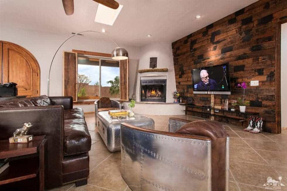 This is the spacious living room with a wall-mounted TV on the patterned wooden wall across from the sofa set and coffee table. Image courtesy of Toptenrealestatedeals.com.