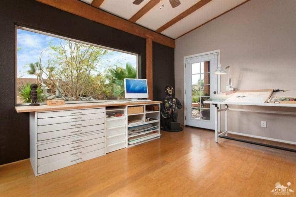 This is the spacious studio and home office. It has light cabinetry to match the artist's table against the gray wall. These are complemented by the hardwood flooring. Image courtesy of Toptenrealestatedeals.com.