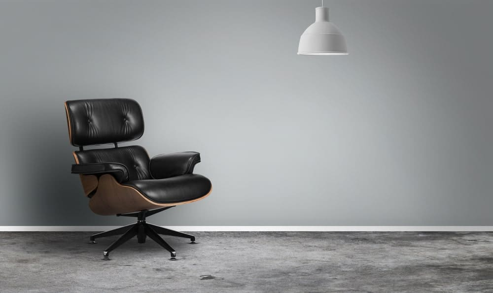 Gray interior with black leather office chair and a white dome pendant.