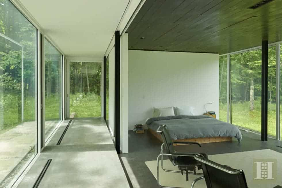 This is the bedroom that has a large platform bed complemented by the gray floor and gray ceiling. These are then brightened by the natural lights of the glass walls. Image courtesy of Toptenrealestatedeals.com.
