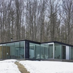 This is an exterior view of the house that showcases its glass walls that give glimpses of the bright interiors. These are then complemented by the surrounding landscape. Image courtesy of Toptenrealestatedeals.com.