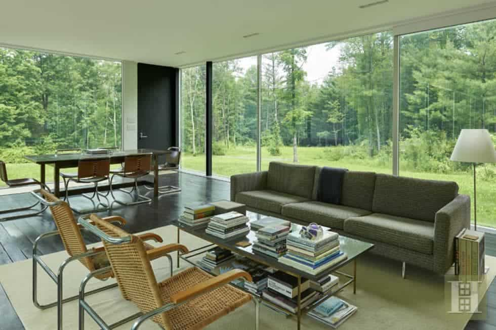 This is the living room and dining area area in a large open-style room surrounded by glass walls. The living room area has a gray sofa paired with a glass-top coffee table and couple of armchairs. Image courtesy of Toptenrealestatedeals.com.