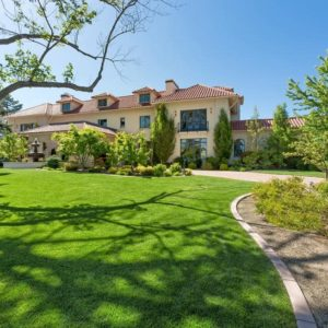 This is a view of the front of the house that has a large grass lawn on its front yard. This pairs with the lush landscaping to complement the beige exteriors of the house that has multiple windows and dormer windows. Image courtesy of Toptenrealestatedeals.com.