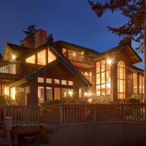 This is the view of the front of the house showcasing the abundance of large glass windows and glass walls that glow warmly from the interior lights. Image courtesy of Toptenrealestatedeals.com.