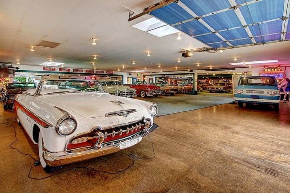 This is a look at the large garage showroom filled with 300 vintage cars on a brown flooring and under a beige ceiling. Image courtesy of Toptenrealestatedeals.com.