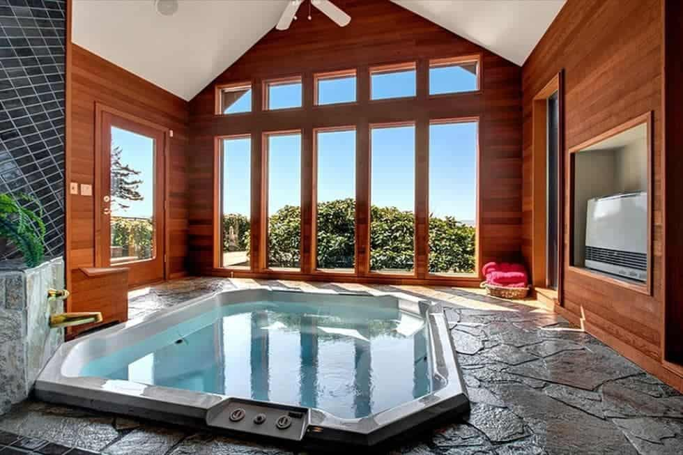This is the spacious room of the hot tub with a tall cathedral ceiling complemented by the wood-paneled walls dominated by tall windows that bring natural lighting for the hot tub that is embedded onto the mosaic stone floor. Image courtesy of Toptenrealestatedeals.com.