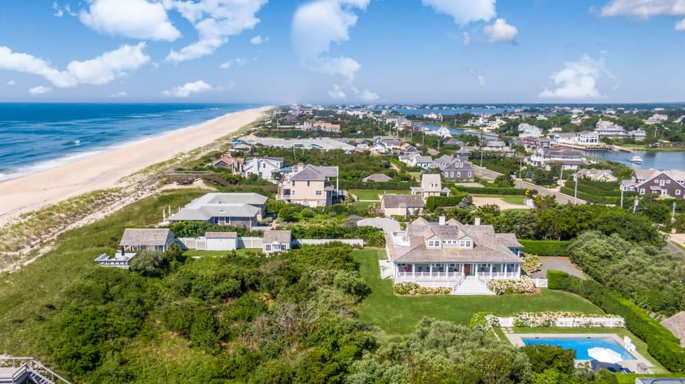 This is an aerial view of the house showcasing its light exterior tones that make it stand out against the surrounding green landscaping, a swimming and a garden. Image courtesy of Toptenrealestatedeals.com.