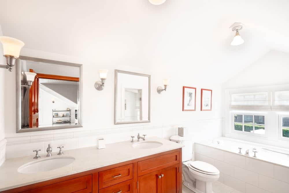 This is the bathroom with a dark wooden vanity contrasted by the white countertop that matches with the walls and ceiling. This vanity is then topped with a couple of wall-mounted mirrors and sconces. Image courtesy of Toptenrealestatedeals.com.