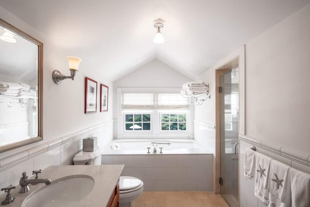 This other view of the bathroom showcases the bathtub at the far end under the windows and the white cathedral ceiling with a simple lighting in the middle. Image courtesy of Toptenrealestatedeals.com.