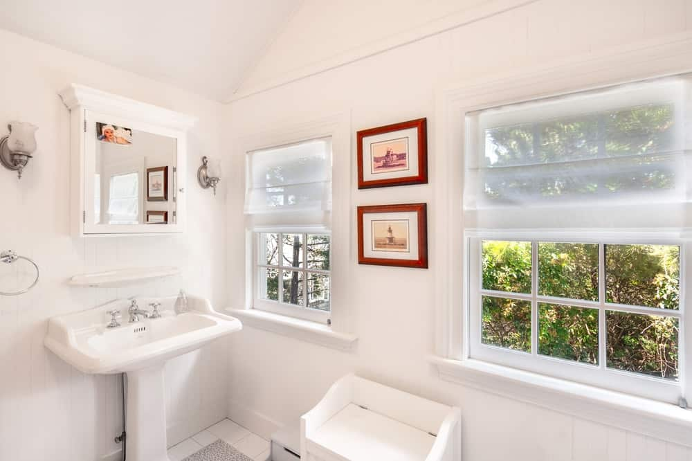 This other bathroom has a white porcelain pedestal sink by the couple of windows that is adorned with framed artworks and the lush landscaping outside. Image courtesy of Toptenrealestatedeals.com.