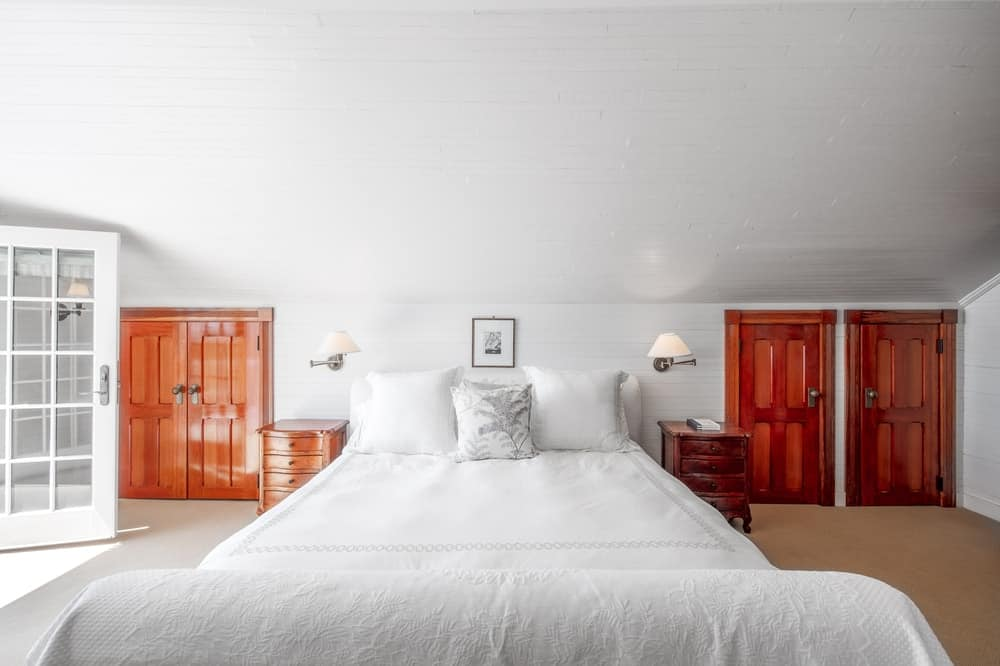 This other angle of the bedroom showcases the wooden doors on other side of the bed that has white sheets and is flanked by wooden bedside drawers. Image courtesy of Toptenrealestatedeals.com.